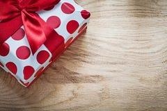 Actuel enfermé dans une boîte avec le ruban rouge sur le conce de célébrations de conseil en bois Images libres de droits