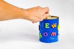 Acuñe el parte movible en una caja de dinero hecha a mano con la nueva inscripción casera en un fondo blanco Fotos de archivo libres de regalías