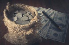 Acuñe en saco de yute con el dinero y la pluma Imagen de archivo libre de regalías