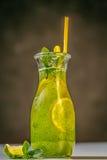 Acuñe la limonada en el jarro con la paja y los limones amarillos en la tabla al aire libre Foto de archivo