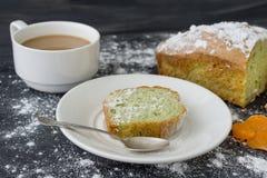 Acuñe la torta asperjada con el azúcar en polvo en superficie oscura con la taza de café Imagen de archivo