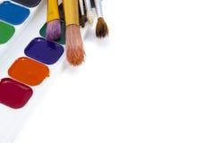 Acuarelas brillantes de las pinturas con los cepillos aislados en blanco Imagen de archivo
