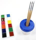 Acuarelas, cepillos y un vidrio-pote Imagen de archivo libre de regalías