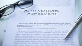 Acuerdo conjunto que miente en la tabla, la pluma y las lentes en el documento oficial imágenes de archivo libres de regalías