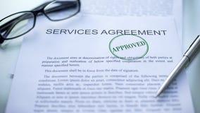 Acuerdo de servicios aprobado, sello sellado en el documento oficial, negocio fotografía de archivo libre de regalías