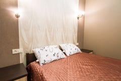 Acueste con una manta marrón y las almohadas, sitio Foto de archivo libre de regalías