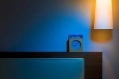 Acueste el cabecero, la lámpara, el reloj, y los vidrios de lectura en la noche Imágenes de archivo libres de regalías