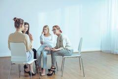 Acueste hablar con las mujeres jovenes durante el entrenamiento en la oficina foto de archivo