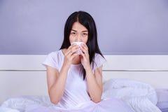 Acup женщины выпивая кофе на кровати в спальне Стоковая Фотография