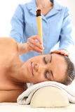 Acupressure, alternative medicine, natural medicine. Woman relaxes in the study of natural medicine. ear candling treatment Stock Image