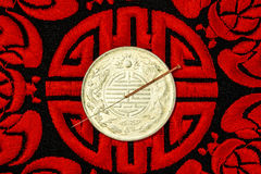 Acupuncture needle on Chinese coin and symbol for immortality Royalty Free Stock Photography