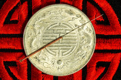 Acupuncture needle on Chinese coin and symbol for immortality Stock Photography