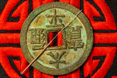 Acupuncture needle on Chinese coin and symbol for immortality Stock Images