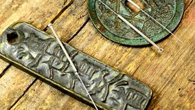 Acupuncture needles on antique Chinese coins