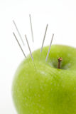 Acupuncture needles in Apple Stock Photo