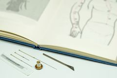 Acupuncture needles and textbook. Acupuncture needles, moxa cone, ear needles, knife and textbook Royalty Free Stock Photos