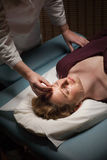 Acupuncture patient. Female acupuncture patient receiving treatment to her face Stock Image