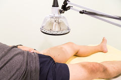 Acupuncture patient being treated with needles and infrared heat Royalty Free Stock Photos