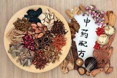Acupuncture Therapy and Chinese Herbs. Chinese acupuncture needles with traditional herbs used in herbal medicine with calligraphy script on bamboo background stock photos