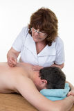 Acupuncturist placing needle on man's back Stock Photo