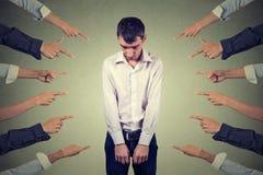 Acusação do indivíduo culpado Homem triste da virada que olha abaixo de muitos dedos que apontam nele fotografia de stock