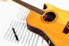 Acustic Guitar. With the score  on a white background Royalty Free Stock Photography