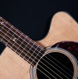 Acustic Guitar Isolated On Black. An acoustic guitar isolated against a low key black background in the square format Stock Image