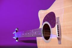 Acustic Guitar Isolated On Blue. An acoustic guitar isolated against a purple background in the horizontal format Stock Images