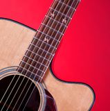 Acustic Guitar Isolated On Red. An acoustic guitar isolated against a red background in the square format Royalty Free Stock Photography
