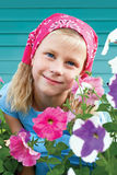 Acute little girl in a garden on a background of turquoise fence Royalty Free Stock Images