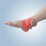 Acute pain in ankle. Woman holding hand to spot of ankle-aches. Stock Photography