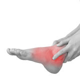 Acute pain in ankle. Woman holding hand to spot of ankle-aches. Royalty Free Stock Photos