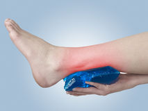 Acute pain in ankle. Woman holding hand to spot of ankle-aches. Royalty Free Stock Image