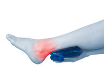 Acute pain in ankle. Woman holding hand to spot of ankle-aches. Royalty Free Stock Photography
