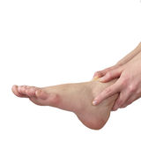 Acute pain in ankle. Woman holding hand to spot of ankle-aches. Stock Images