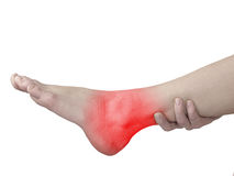 Acute pain in ankle. Woman holding hand to spot of ankle-aches. Royalty Free Stock Photo