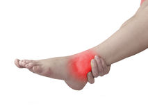 Acute pain in ankle. Woman holding hand to spot of ankle-aches. Stock Photo