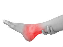 Acute pain in ankle. Woman holding hand to spot of ankle-aches. Royalty Free Stock Images