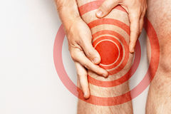 Acute pain in a knee joint, close-up. Color image,  on a white background. Pain area of red color. Man with pain in the knee joint massages the place of acute Stock Photography