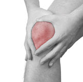 Acute pain in a man  knee. Male holding hand to spot of knee-ach Stock Photos