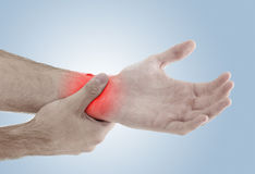 Acute pain in a man palm. Male holding hand to spot of palm-ache Stock Images