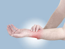Acute pain in a man wrist. Male holding hand to spot of wrist pa Royalty Free Stock Images