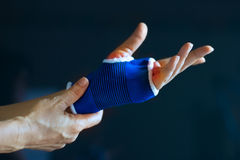Acute pain in a senior hand wrist, safty in a bandage from stretch, colored in red on dark blue background Royalty Free Stock Photo
