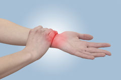 Acute pain in a woman wrist. Female holding hand to spot of wris Royalty Free Stock Photography