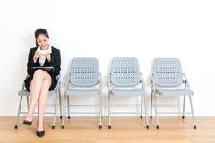 Adáptese al modelo femenino que se sienta en la silla de madera del piso imágenes de archivo libres de regalías