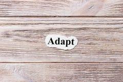 Adáptese de la palabra en el papel Concepto Las palabras de se adaptan en un fondo de madera imagenes de archivo