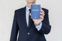 Adáptese encima del hombre de negocios que sostiene el pasaporte universal en mano derecha fotografía de archivo