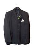 Adáptese a la chaqueta que cuelga en una percha con un boutonniere imagen de archivo