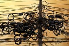 Ad alta tensione, energia elettrica di groviglio del cavo sull'atmosfera di sera del fondo del cielo, cavo di alimentazione ad al Immagini Stock Libere da Diritti