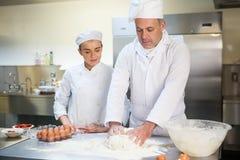 Ad apprendista del cuoco unico capo mostrando come preparare pasta Immagini Stock